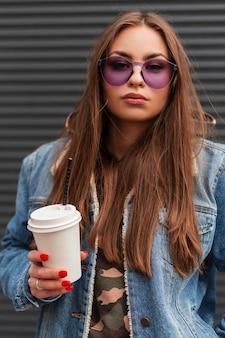 Mode portret amerikaanse jonge vrouw hipster in stijlvolle jeugd paarse bril in modieuze blauwe denim jasje met een warme drank in handen in de buurt van grijze muur op straat. mooi meisjesmodel in de stad.