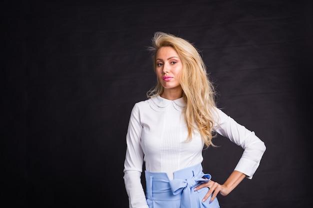 Mode, portret en mensen concept - jonge blonde vrouw permanent over de zwarte achtergrond met