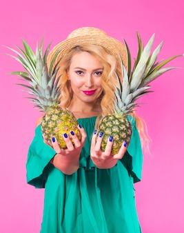 Mode portret jonge mooie vrouw met ananas over roze muur