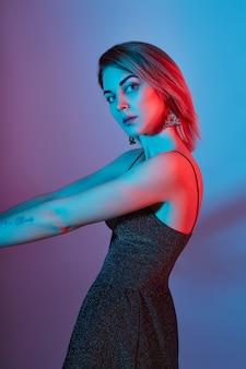 Mode portret meisje licht neon lampen blauw rode kleur. vrouw het stellen op gekleurde, mooie make-up.