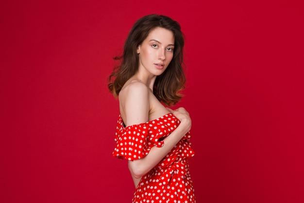 Mode portret van aantrekkelijke jonge vrouw in rode gestippelde jurk op rode studio