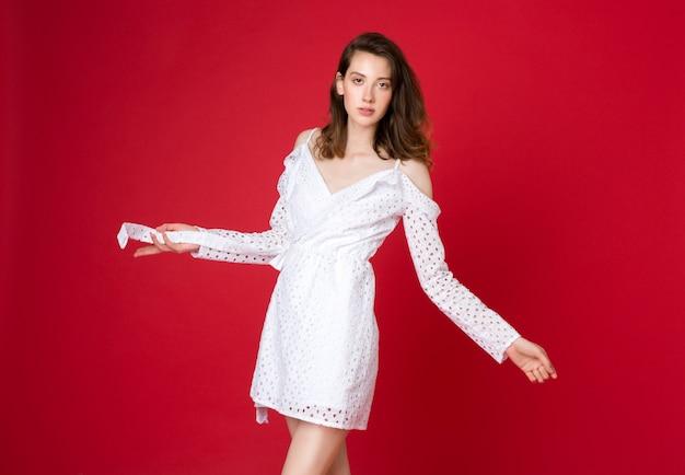 Mode portret van aantrekkelijke jonge vrouw in witte katoenen jurk op rode studio