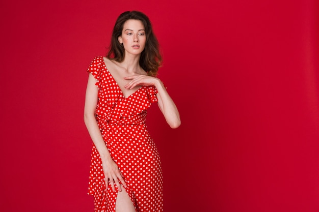 Mode portret van aantrekkelijke lachende jonge vrouw in rode gestippelde jurk op rode studio