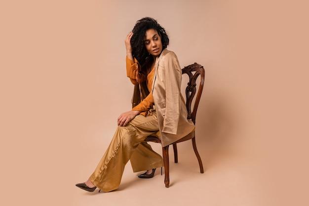 Mode portret van aantrekkelijke vrouw met bruine huid met perfect krullende haren in elegante oranje blouse en zijden broek zittend op vintage stoel op beige muur.