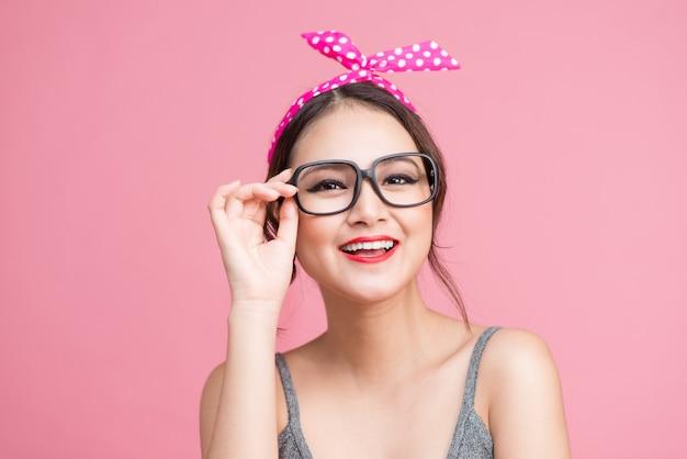 Mode portret van aziatisch meisje met zonnebril permanent op roze achtergrond.
