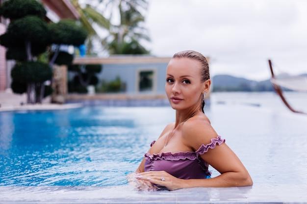 Mode portret van blanke vrouw in bikini in blauw zwembad op vakantie bij dag natuurlijk licht