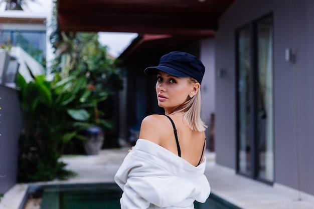 Mode portret van blonde kaukasische stijlvolle vrouw in frans glb blazer en korte broek buiten buiten villa