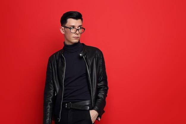 Mode portret van de jonge knappe man. zwart leren jasje, poloneck, bril, donkerbruin haar, rode achtergrond