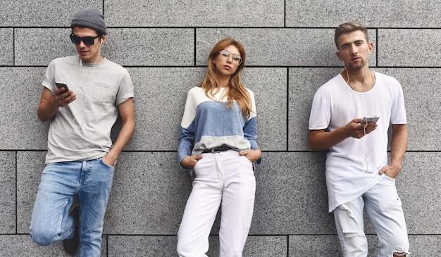 Mode portret van drie beste vrienden poseren op straat, stijlvolle outfit en jeans dragen tegen grijze muur.