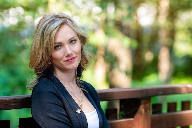 Mode portret van een elegante, mooie, glimlachende blonde vrouw op een onscherpe parkachtergrond