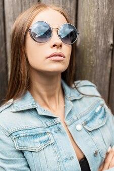 Mode portret van een glamour mooi meisje model met een kaukasisch gezicht in modieuze zonnebril in een spijkerjasje staat in de buurt van een houten muur