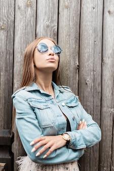 Mode portret van een grappige mooie jonge vrouw in vintage blauwe ronde zonnebril met stijlvol jeans jasje staat in de buurt van een houten muur