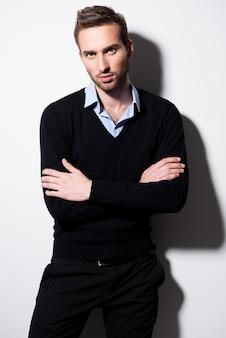 Mode portret van een jonge man in zwarte trui en blauw shirt met gekruiste armen.