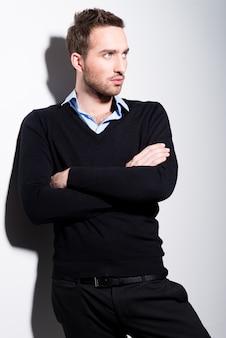 Mode portret van een jonge man in zwarte trui en blauw shirt met gekruiste armen