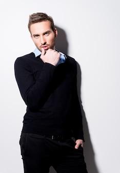 Mode portret van een jonge man in zwarte trui en blauw shirt met hand in de buurt van gezicht.