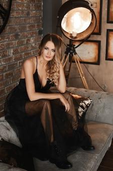 Mode portret van een jonge model vrouw in casual zwarte jurk en zwarte laarzen zit op de vintage bank