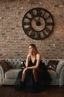 Mode portret van een jonge mooie vrouwelijke model in casual zwarte jurk en zwarte laarzen zit op de vintage bank