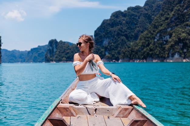 Mode portret van een jonge vrouw in witte top en broek op vakantie, op thaise houten zeilboot. reis concept. vrouwtje in khao sok national park.