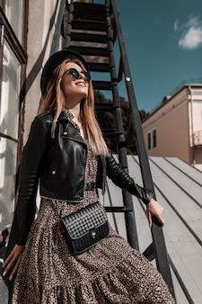 Mode portret van een mooi jong meisje model met zonnebril in stijlvolle kleding met een vintage jurk, leren jas, hoed en handtas op een metalen trap op een zonnige dag. vrouwelijke schoonheid en stijl