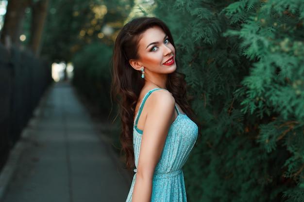 Mode portret van een mooi lachend meisje in een turquoise jurk in het park