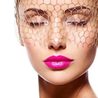 Mode portret van een mooi meisje draagt sluier voor ogen. lichte make-up. geïsoleerd op een witte muur