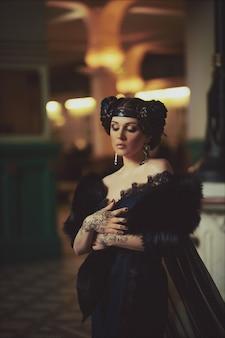 Mode portret van een mooie brunette in een lange jurk en mehndi op haar handen in de bouw van het oude treinstation. creatieve make-up en kapsel