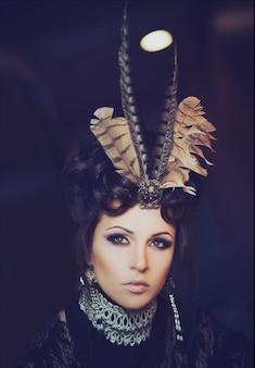 Mode portret van een mooie brunette in een zwarte kanten jurk. creatief make-up en kapsel met veren. halloween