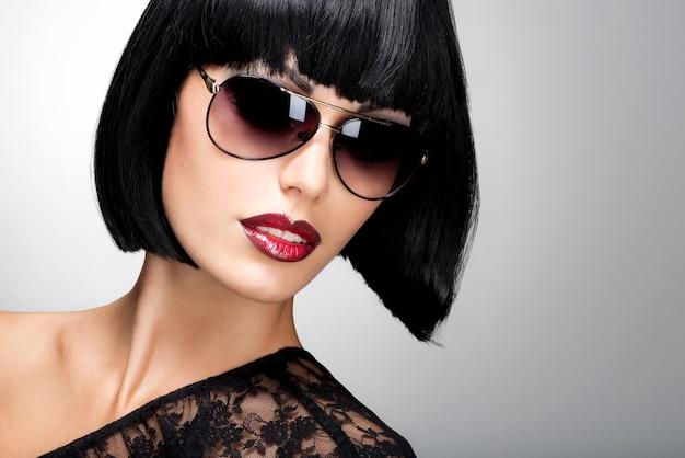 Mode portret van een mooie brunette vrouw met geschoten kapsel met rode zonnebril foto