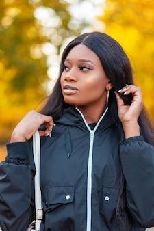 Mode portret van een mooie jonge afro-amerikaanse vrouw in een stijlvolle zwarte jas met een handtas maakt haar haar recht en loopt in het park tegen een achtergrond van kleurrijk geel herfstgebladerte