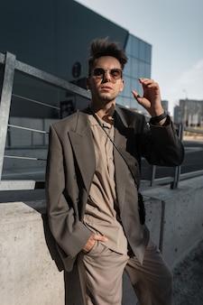 Mode portret van een mooie jonge man model met stoppels in een modieus pak met een jas en shirt zet een zonnebril op in de stad. mannelijke stedelijke zakelijke stijl
