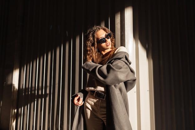 Mode portret van een mooie jonge vrouw met krullend haar met zonnebril in een stijlvolle jas op straat in de buurt van een metalen muur in het zonlicht. stedelijke vrouwelijke stijl