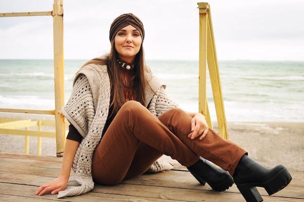 Mode portret van een mooie lachende brunette vrouw zit stad strand, glimlachend en camera kijken