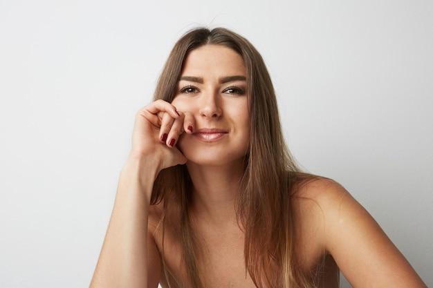 Mode portret van een mooie lachende vrouw met lang haar over lege lichte achtergrond. mode.