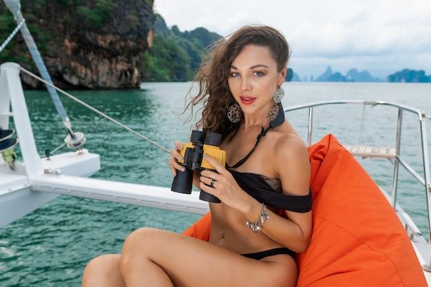 Mode portret van een positieve en mooie vrouw zittend op het oranje kussen