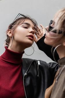 Mode portret van een twee mooie jonge meisjes met zonnebril in een modieuze zwarte leren jas met een gebreide bordeauxrode trui op straat in de buurt van grijze muur