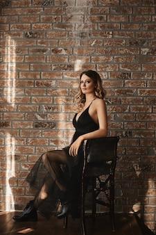 Mode portret van een vrouwelijk model met perfecte avondmake-up, gekleed in een zwarte jurk en zwarte laarzen