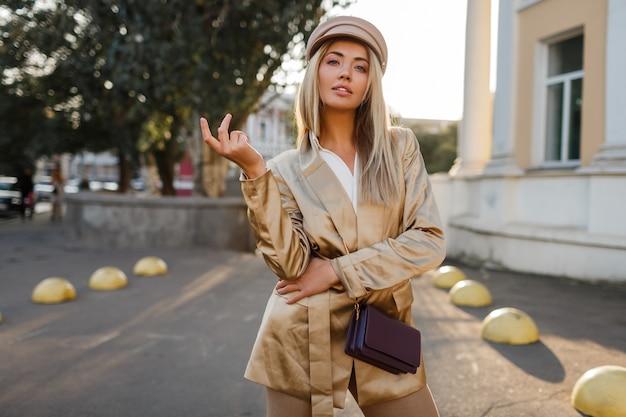 Mode portret van elegante blonde vrouw in lederen hoed en casual beige jas. live; y vrouwelijke poseren buiten. zonsondergang licht. herfst look.