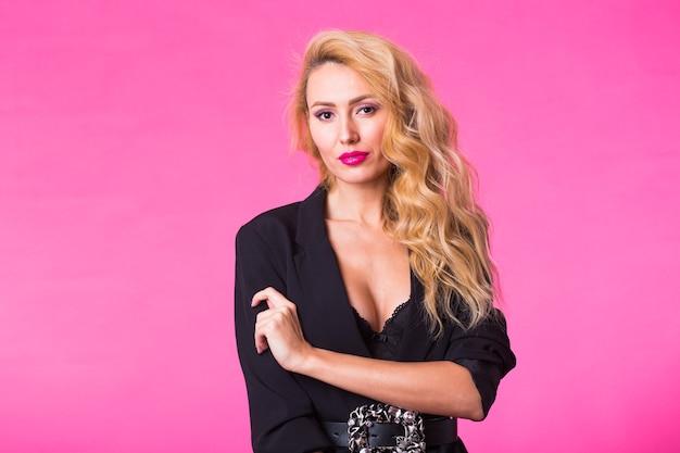 Mode portret van elegante jonge vrouw met blond krullend haar op roze achtergrond