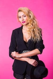 Mode portret van elegante jonge vrouw met blond krullend haar over roze muur