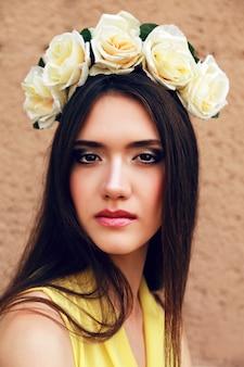 Mode portret van gelukkig speels vrij brunette meisje glimlachend en plezier, pastel gele jurk en rozen krans dragen.