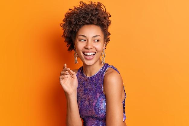 Mode portret van gelukkige stijlvolle vrouw in lichte kleren oorbellen glimlacht in grote lijnen kijkt opzij geïsoleerd over oranje muur