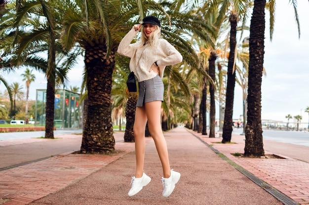 Mode portret van het dragen van een jonge vrouw, pet, leren jas, crossbody tas, minirok, trui en trendy accessoires in promenade