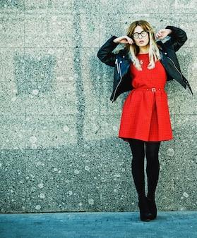 Mode portret van hipster vrouw in stijlvolle casual zomer outfit poseren tegen muur achtergrond.