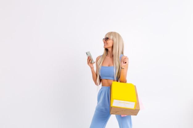 Mode portret van jonge blonde vrouw met lang prachtig steil haar houdt kleurrijke boodschappentassen