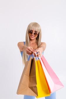 Mode portret van jonge blonde vrouw met prachtig lang steil haar met kleurrijke boodschappentassen in de studio op een wit.