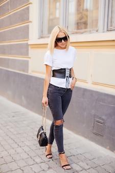 Mode portret van jonge elegante blonde vrouw buiten. grijze jurk, leren rugzak, zonnebril
