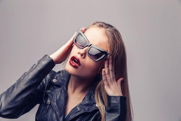 Mode portret van jonge elegante vrouw in zwart lederen jas, zonnebril.