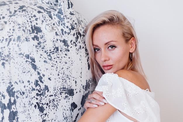 Mode portret van jonge europese vrouw met blonde haren in witte lange zomerjurk