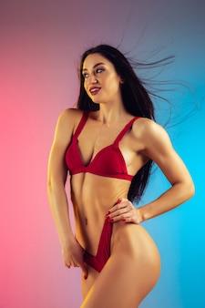 Mode portret van jonge fit en sportieve vrouw in stijlvolle rode luxe badmode op gradiënt muur perfect lichaam klaar voor de zomer