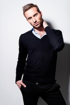 Mode portret van jonge man in zwarte trui en blauw shirt met contrast schaduwen.